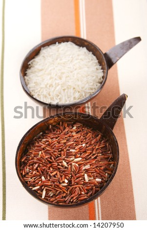Himalayan Red Long grain and white Rice in coconut bowl on tablecloth, shallow DOF - stock photo