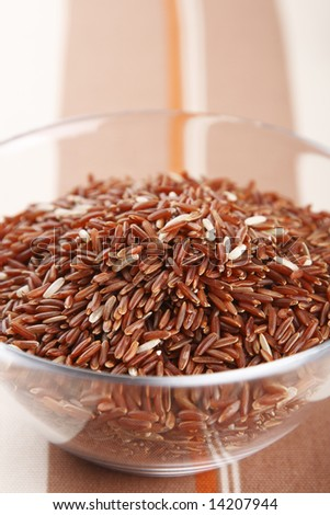 Himalayan Red Long grain Rice in glass bowl, shallow DOF - stock photo