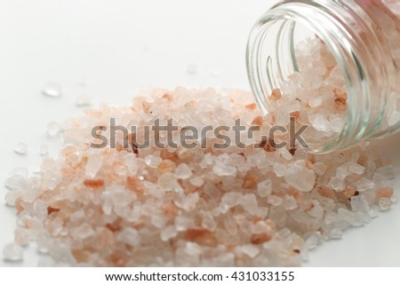 Himalayan salt in small jar of glass.. Pink and orange coarse crystals.