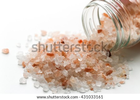 Himalayan salt in small jar of glass. Pink and orange coarse crystals.
