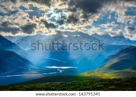 HImalayan valley landscape with Himalayas mountains. Sun rays come through clouds. Himachal Pradesh, India - stock photo