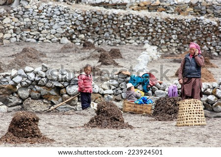 HIMALAYAS, NEPAL, MARCH 23: Nepali woman and children in field working. Everest region, Himalayas, in Nepal on March 23, 2014 - stock photo