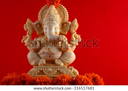 Hindu God Ganesha. Ganesha Idol on Red Background with flowers.  - stock photo