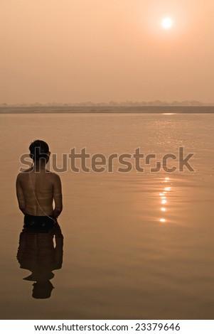 Hindu pilgrim take a bath in the ganges river in Varanasi, India. - stock photo