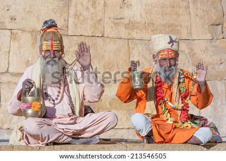 Hindu sadhu holy man, sits on the ghat - stock photo