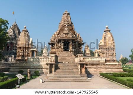 Hindu temple, built by Chandela Rajputs, at Western site in India's Khajuraho. Beige brown heap of stones artfully stacked against blue skies. - stock photo