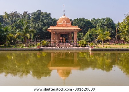 Hindu temple of Lord Jagannath with reflection across holy pond at Mayapur, India. - stock photo