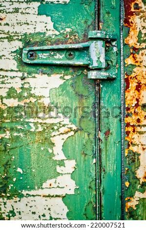 Hinge on rusty metal door. Textured door with cracked paint. Green painted door detail. - stock photo