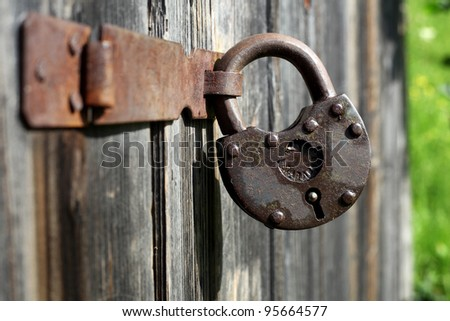 Hinged lock on the old shed - stock photo