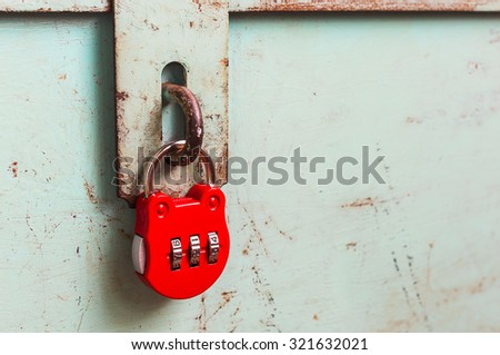 Hinged lock with red combination padlock on grunge steel box - stock photo