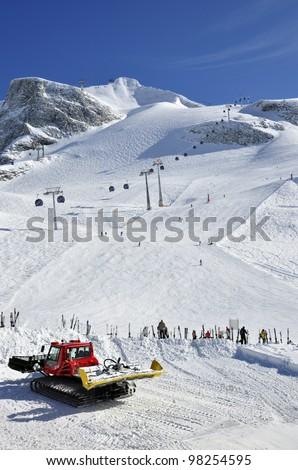 Hintertux Glacier, gondola cable car, snow groomer, ski runs and skiers in Zillertal Alps in Austria - stock photo
