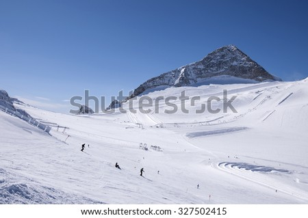Hintertux Glacier with skiers, snowboarders, ski runs, pistes and ski lifts in Zillertal Alps in Austria - stock photo