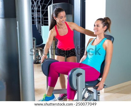 Hip abduction women exercise at gym indoor workout and personal trainer smiling - stock photo