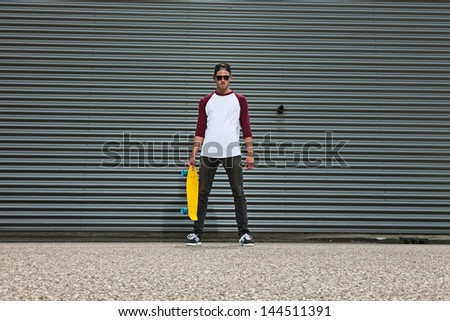 Hip cool urban fashion skateboarder with woolen hat on the street in front of iron wall. - stock photo