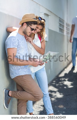 Hip couple checking map and leaning against wall in the city