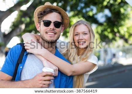 Hip couple embracing and smiling at the camera outdoors - stock photo
