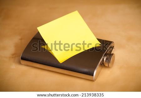 Hip flask with empty sticky note - stock photo