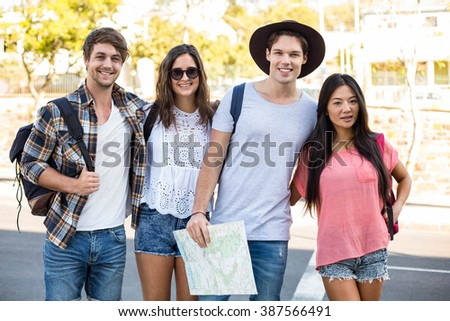 Hip friends smiling at the camera outdoors