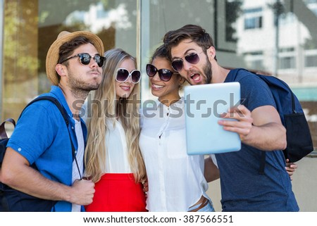 Hip friends taking selfie with tablet in the city - stock photo