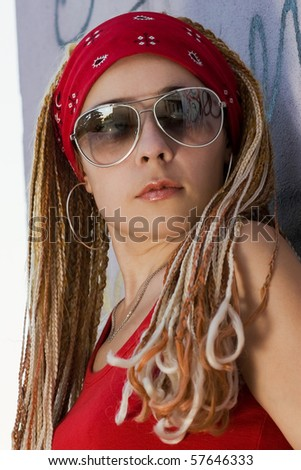 Hip-hop chick posing at the graffiti sprayed wall outdoors - stock photo
