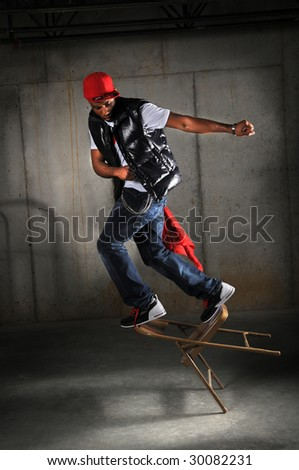 Hip hop dancer performing falling on chair over industrial background - stock photo