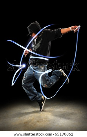 Hip hop dancer performing with LED lights dancing over dark background with spotlight - stock photo