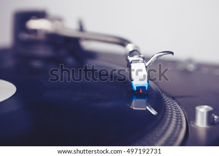 Hip hop DJ turtnable playing records with music. Vinyl record for scratching tracks. Close up.Pro audio equipment for disc jockey,house party or nightclub event.Macro