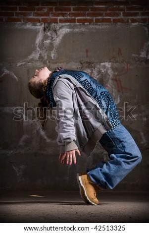 Hip hop girl dancing in modern style over urban grey brick wall - stock photo