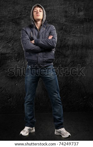 hip-hop guy looks down. On the background wall - stock photo