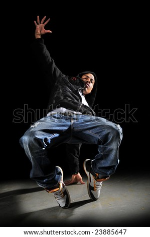 Hip hop man dancing over a dark background - stock photo