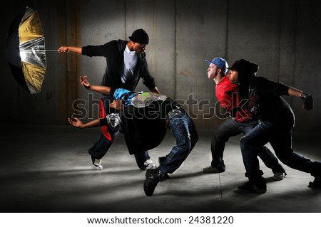 Hip hop men performing and act over an urban background - stock photo