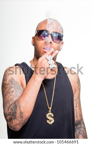 Hip hop urban gangster black man wearing dark shirt and golden jewelry isolated on white. Smoking cigarette. Looking confident. Cool guy. Studio shot. - stock photo