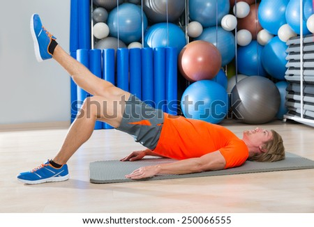 hip lift with leg extension blond man at gym workout with swiss ball background - stock photo