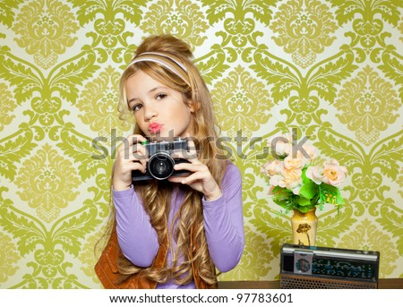 hip retro little girl shooting photo with vintage camera on wallpaper - stock photo