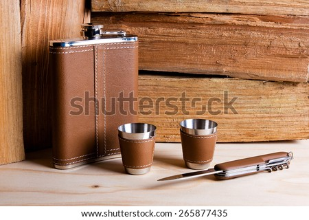 Hip stainless flask, cups and knife decorated leather on wooden background. - stock photo