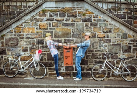 Hip young couple dancing by brick wall with their bikes on a sunny day in the city - stock photo