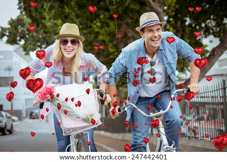 Hip young couple going for a bike ride against red heart balloons floating - stock photo