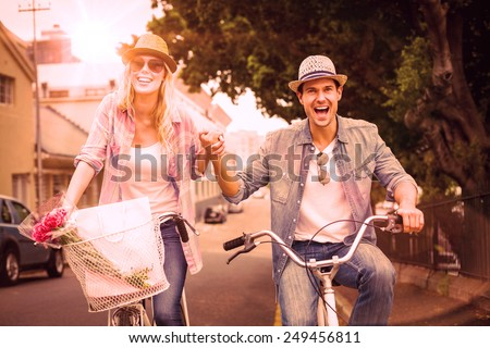 Hip young couple going for a bike ride on a sunny day in the city - stock photo