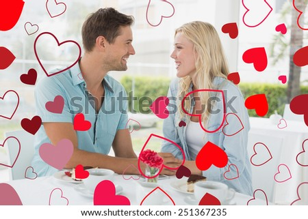 Hip young couple having desert and coffee together against valentines heart design - stock photo