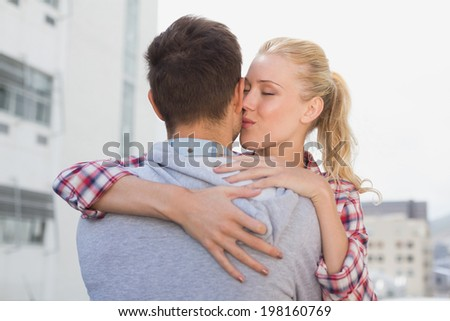 Hip young couple hugging with woman kissing his cheek on a sunny day in the city - stock photo