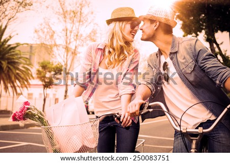 Hip young couple on a bike ride on a sunny day in the city - stock photo