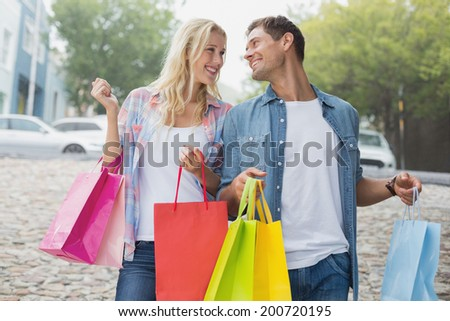 Hip young couple on shopping trip on a sunny day in the city - stock photo