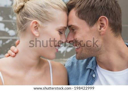 Hip young couple sitting on steps smiling at each other on a sunny day in the city