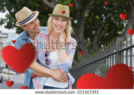 Hip young couple smiling at camera by railings against hearts - stock photo