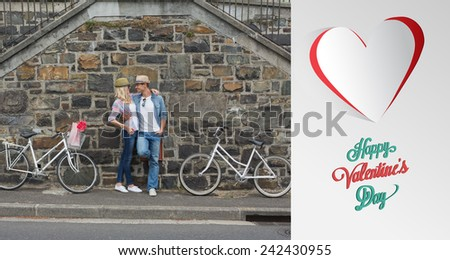 Hip young couple standing by brick wall with their bikes against cute valentines message - stock photo