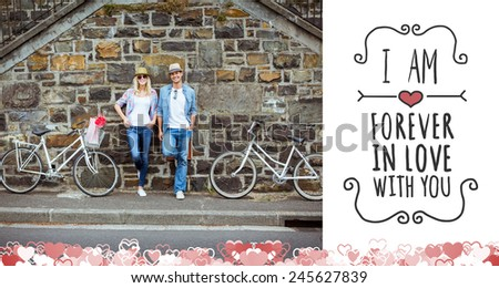 Hip young couple standing by brick wall with their bikes against valentines message - stock photo