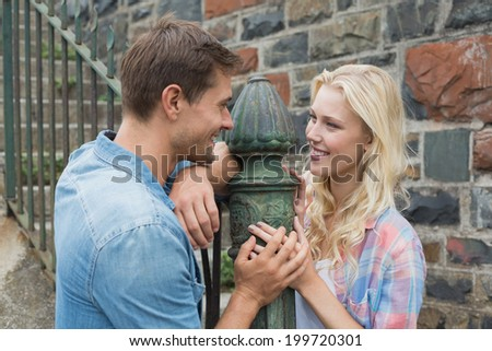 Hip young couple standing by railings on a sunny day in the city - stock photo