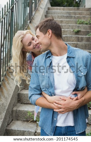 Hip young couple standing by steps hugging on a sunny day in the city