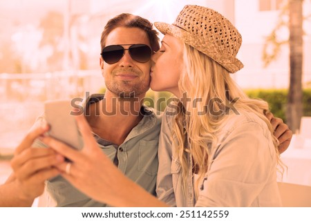 Hip young couple taking a selfie together on the cafe terrace on sunny day - stock photo