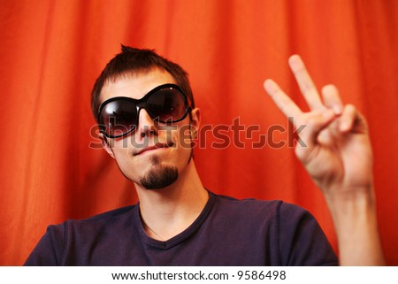 Hip young man showing V sign - stock photo